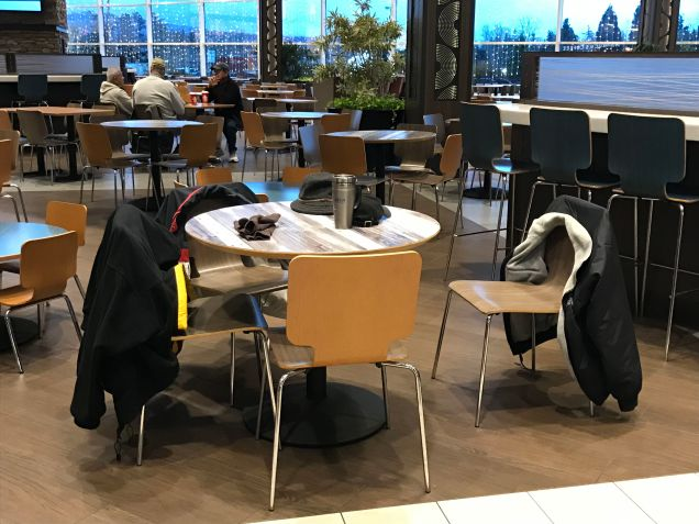 As people warm up, they leave their coats and hats on the food court chairs